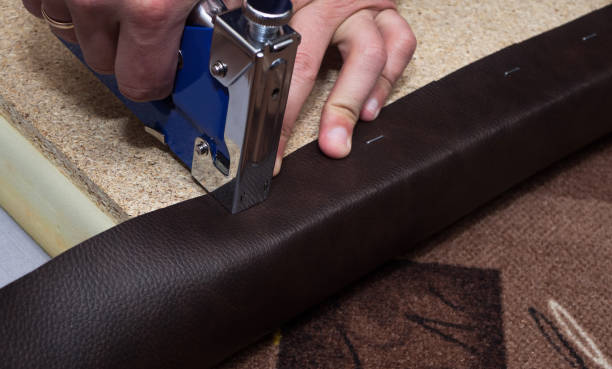 Craftsman fastening leather to the paricle board using staples and stapler stock photo