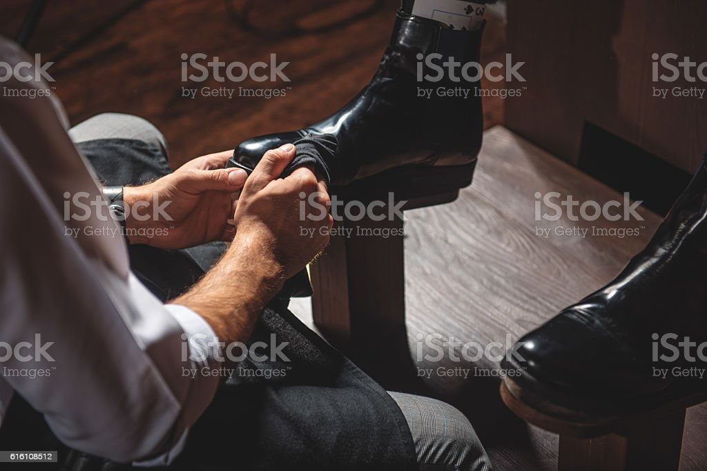 craftsman hands preparing boots for polishing stock photo