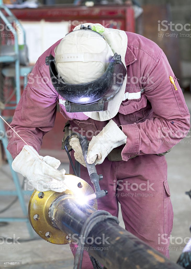 Craftsman in a safety suit is welding a metal pipe stock photo