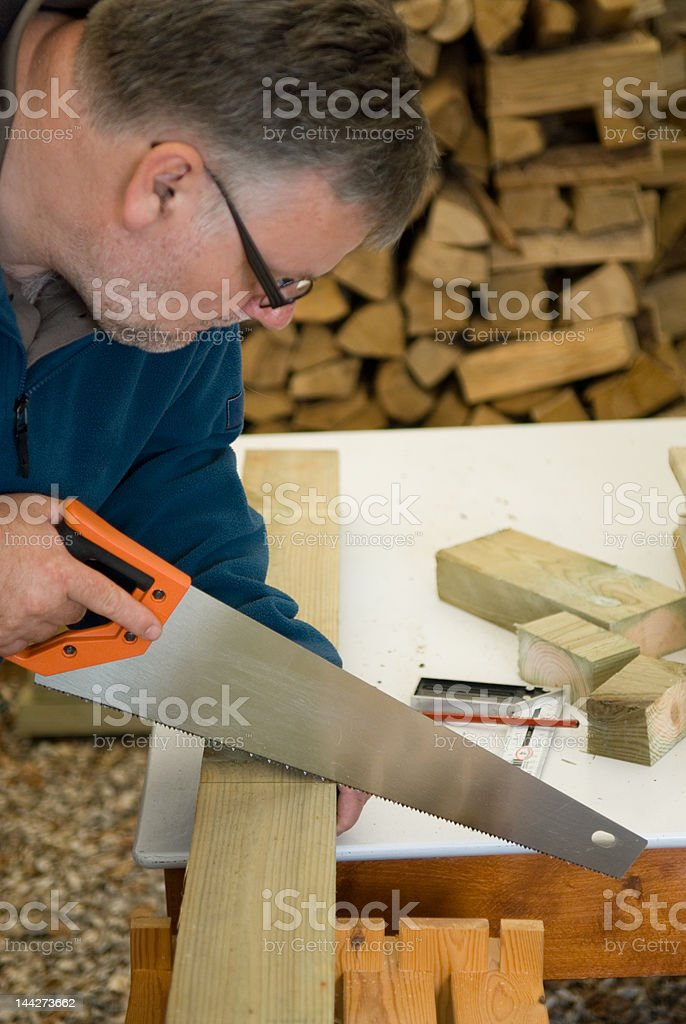 DIY craftsman is cutting wood with a saw stock photo