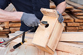Craftsman making a wooden birdhouse with tools or equipment and wood plank all around, hands