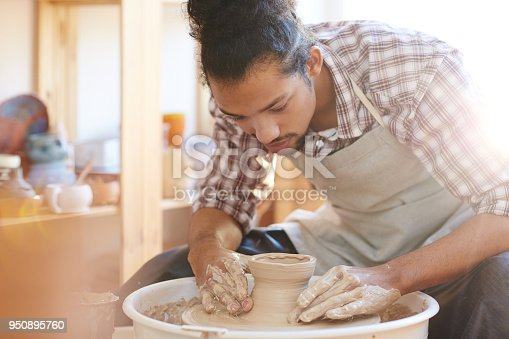 Portrait of young handsome mixed race male potter making clay vase on spinning pottery wheel in workshop