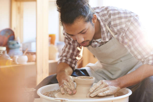 Craftsman making pottery ware Portrait of young handsome mixed race male potter making clay vase on spinning pottery wheel in workshop ceramics stock pictures, royalty-free photos & images