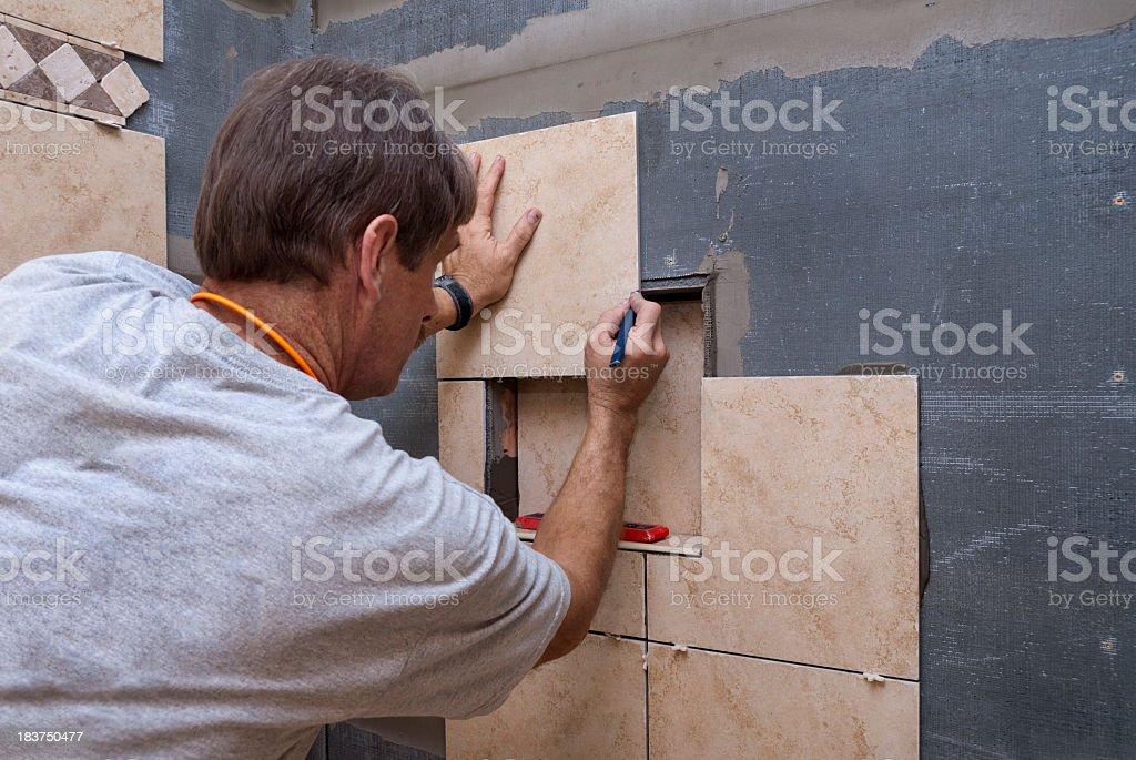 Craftsman Measures Shower Tile During Renovation stock photo