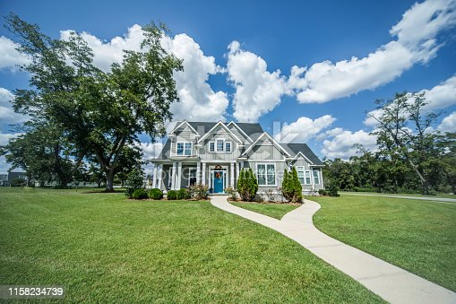A large gray craftsman new construction House with hardy board siding on a large lot with a green lawn on a clear day with a blue sky and lots of clouds. This home has a lot of curb appeal and exterior shrubs, bushes and flowers.