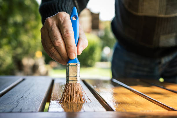 Craftsman painting wooden table stock photo