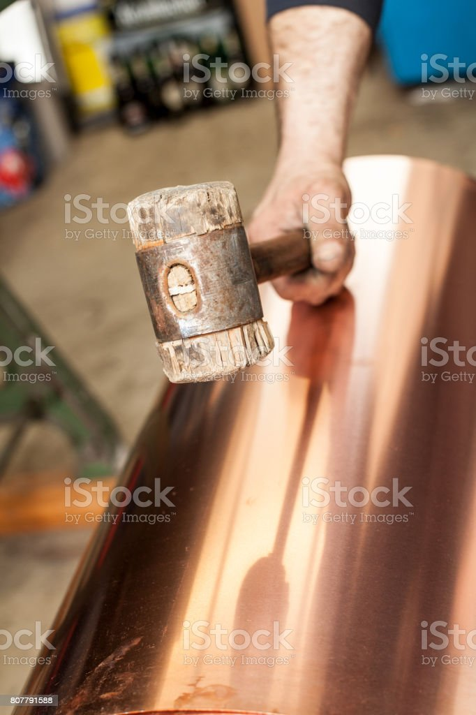 Craftsman plumber with wood hammer Handwork on copper plate stock photo