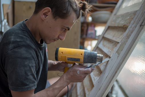 1015564946 istock photo Craftsman repairing old window shades. 1173429852