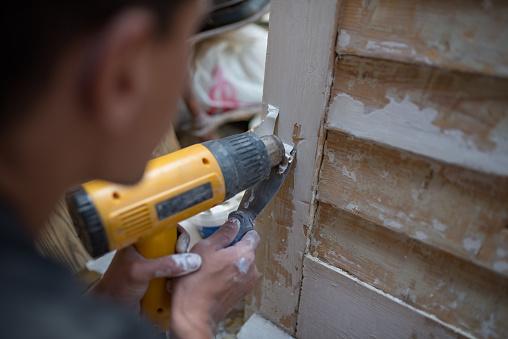 1015564946 istock photo Craftsman repairing old window shades. 1173431033
