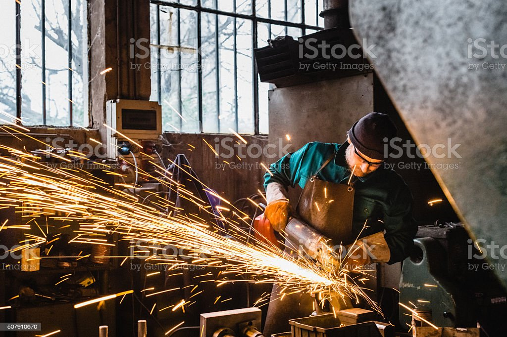 Craftsman repairman working with grinder stock photo