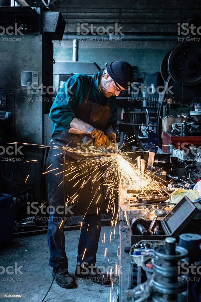 Craftsman repairman working with grinder stock photo