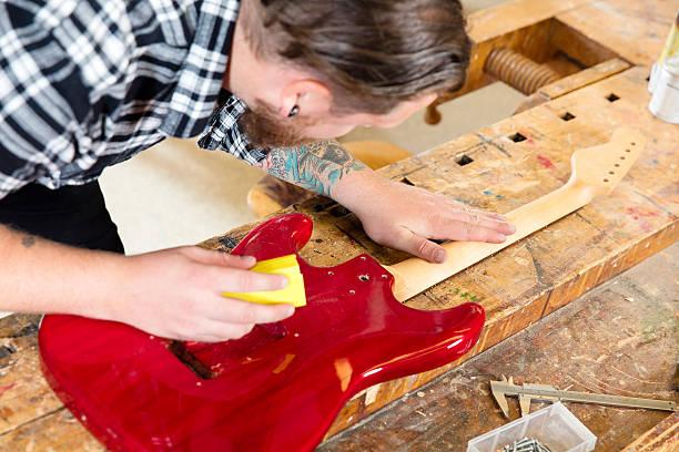 handwerker abgeschmirgelten eine gitarre ausschnitt in holz im workshop - baroque tattoo stock-fotos und bilder