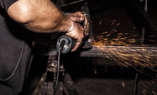 sägen von metall mit disk-mühle in werkstatt handwerker. schleifen von metall mit funken sprühen. - europäisch geschliffene diamanten stock-fotos und bilder