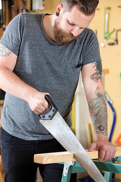 handwerker sägen holz mit hand säge in workshops - baroque tattoo stock-fotos und bilder