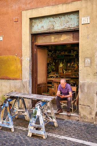 Rome, Italy, June 11 -- A craftsman sitting in front his workshop in an alley of the Rione Monti (Monti district), in the heart of the historic center of Rome. The Monti district is a popular and multi-ethnic quarter much loved by the younger generations and tourists for the presence of trendy pubs, shops and restaurants, where you can find the true soul of the Eternal City. The quarter, located between the Esquiline Hill and the Roman Forum, is also rich in numerous churches and archaeological remains from the Roman era. Image in high definition format.