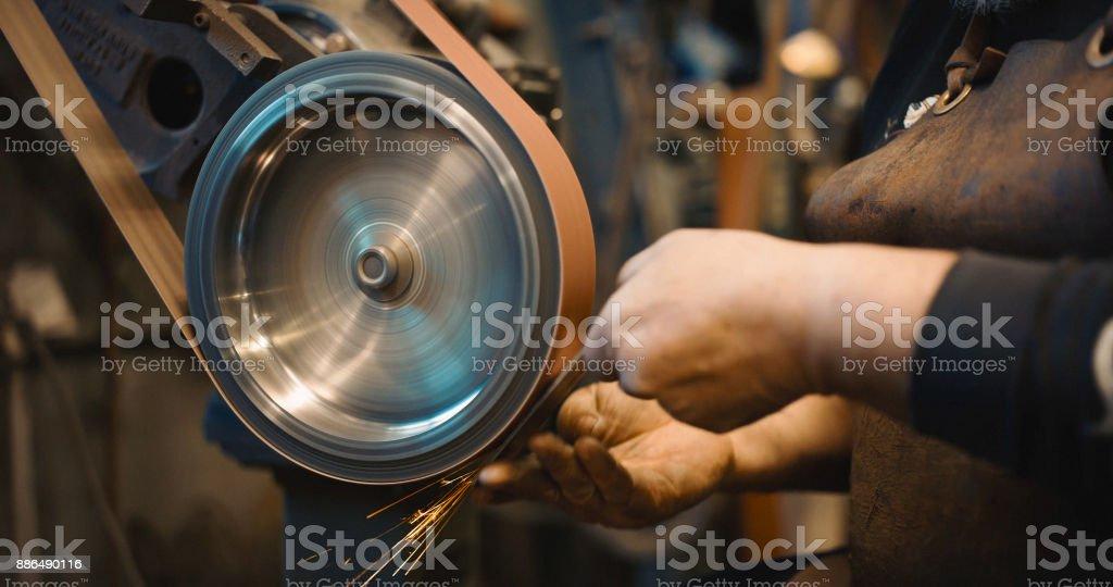 Craftsman uses a belt sander in machine shop. stock photo