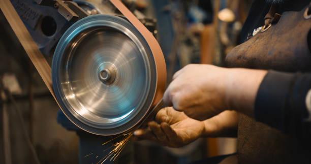 handwerker mit einem gürtel sander-maschine im shop. - schmirgelmaschine stock-fotos und bilder