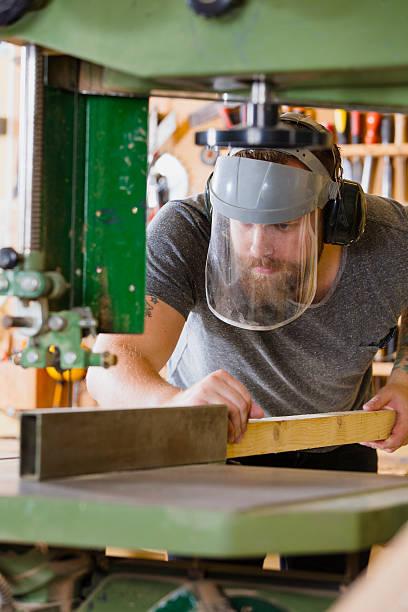 handwerker mit sicherheit maske sonnenblende griffe bandsäge in workshops - baroque tattoo stock-fotos und bilder