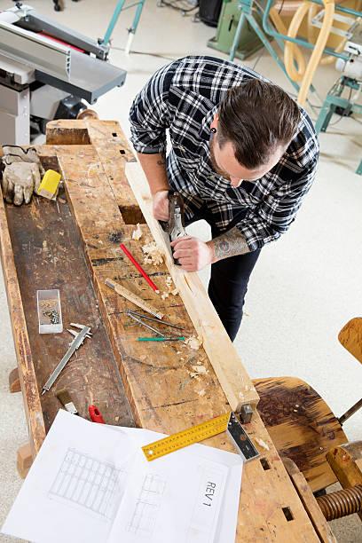 handwerker arbeiten mit flugzeug auf holz plank in workshops - baroque tattoo stock-fotos und bilder