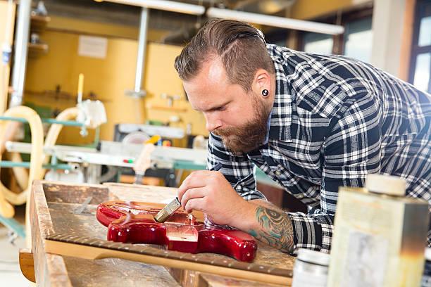 handwerker arbeiten in der werkstatt mit gitarre - baroque tattoo stock-fotos und bilder