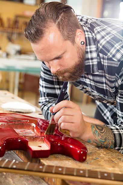 handwerker arbeiten in der werkstatt mit musikinstrumenten - baroque tattoo stock-fotos und bilder