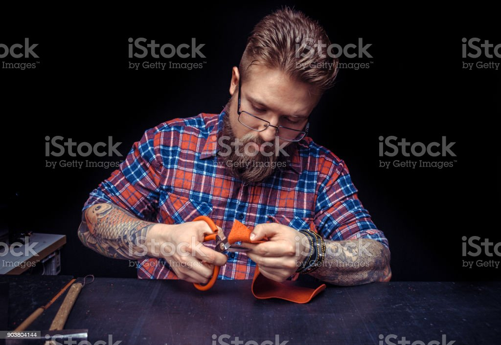 Craftsman working with leather works with leather goods at his desk stock photo