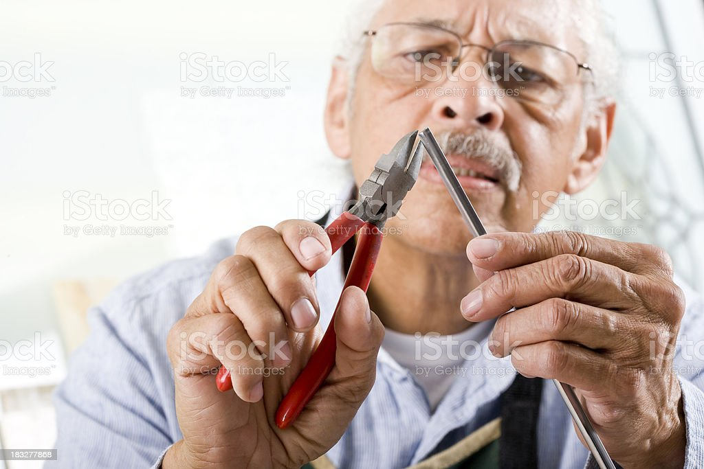 Craftsman working with pliers and metal tube stock photo