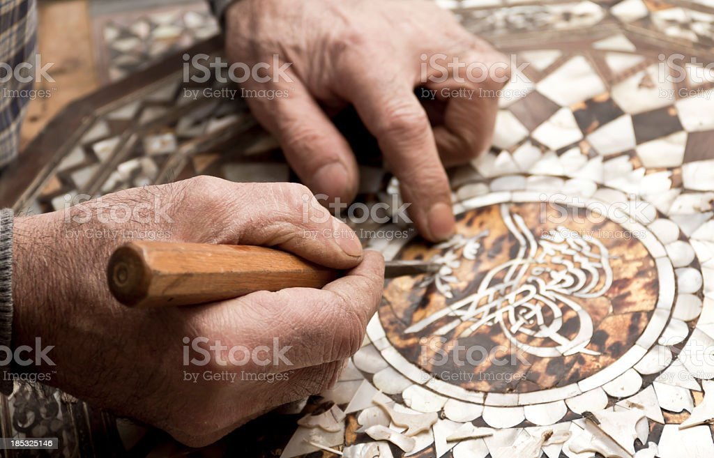 Craftsman's hands repairing a mosaic with sharp tool stock photo