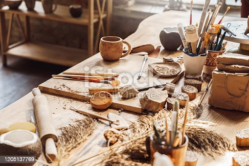 Table with materials and tools for pottery making craftsperson workspace isolated no people creative studio side view close-up