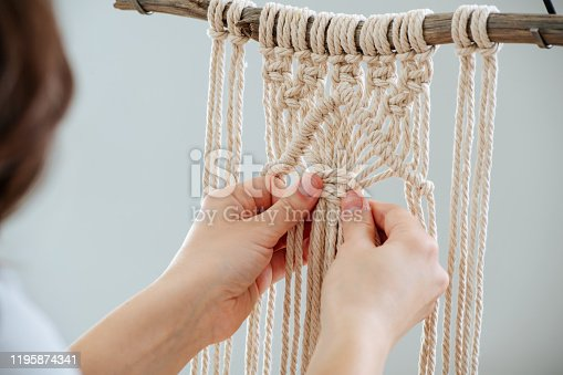 Brunette woman working on a half-finished macrame piece, weaving ropes, making knots. Close up. Cropped. From behind.