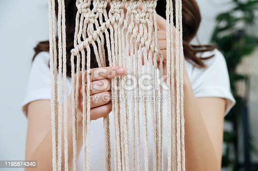 Brunette woman working on a half-finished macrame piece, weaving ropes. Close up. Cropped. No face.