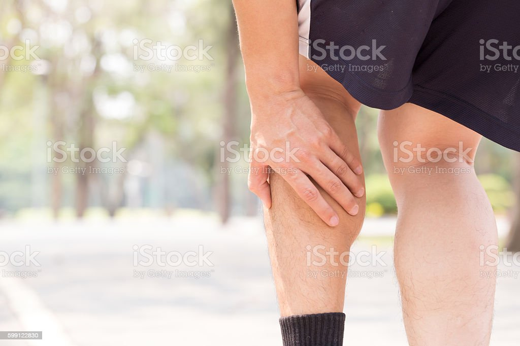 Cramp in leg while exercising. Sports injury concept stock photo