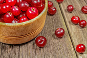 Cranberries in a wooden cup on a wooden table