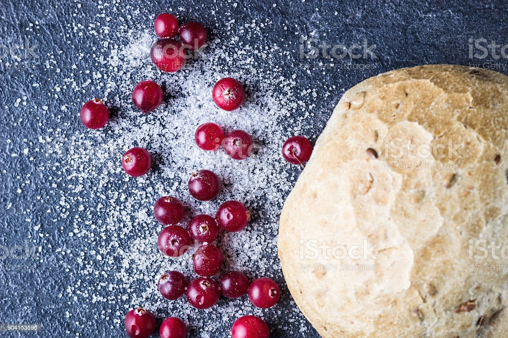 Cranberries in sugar and bun. Directly above. Sweet food.