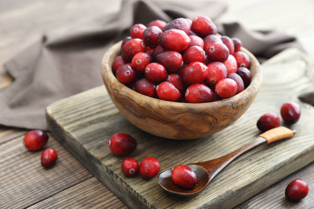 cranberries in wooden bowl - cranberry stock photos and pictures