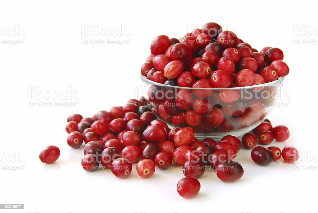 Cranberries overflowing a clear bowl with a white background stock photo