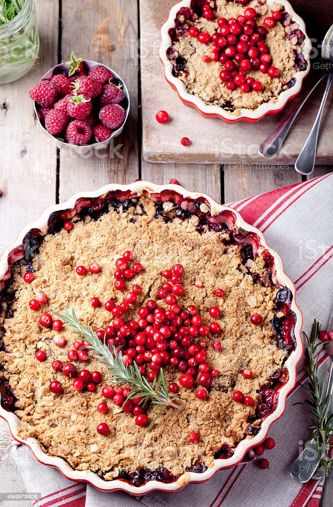 Cranberry, bilberry crumble with rosemary on a wooden background stock photo