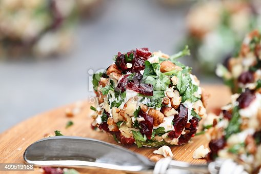 Cranberry nut cheese ball made with cream cheese, goat or feta cheese, parsley, cranberries and chopped pecans over a rustic background. Extreme shallow depth of field with selective focus on center.