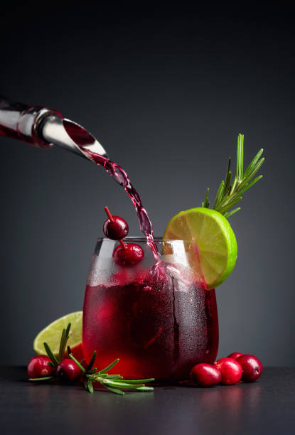 Cranberry cocktail garnished with berries, lime, and rosemary. stock photo