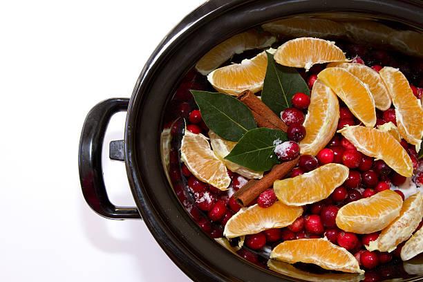 cranberry sauce with oranges, cinnamon and bay leaf simmering in - crock pot süßigkeiten stock-fotos und bilder