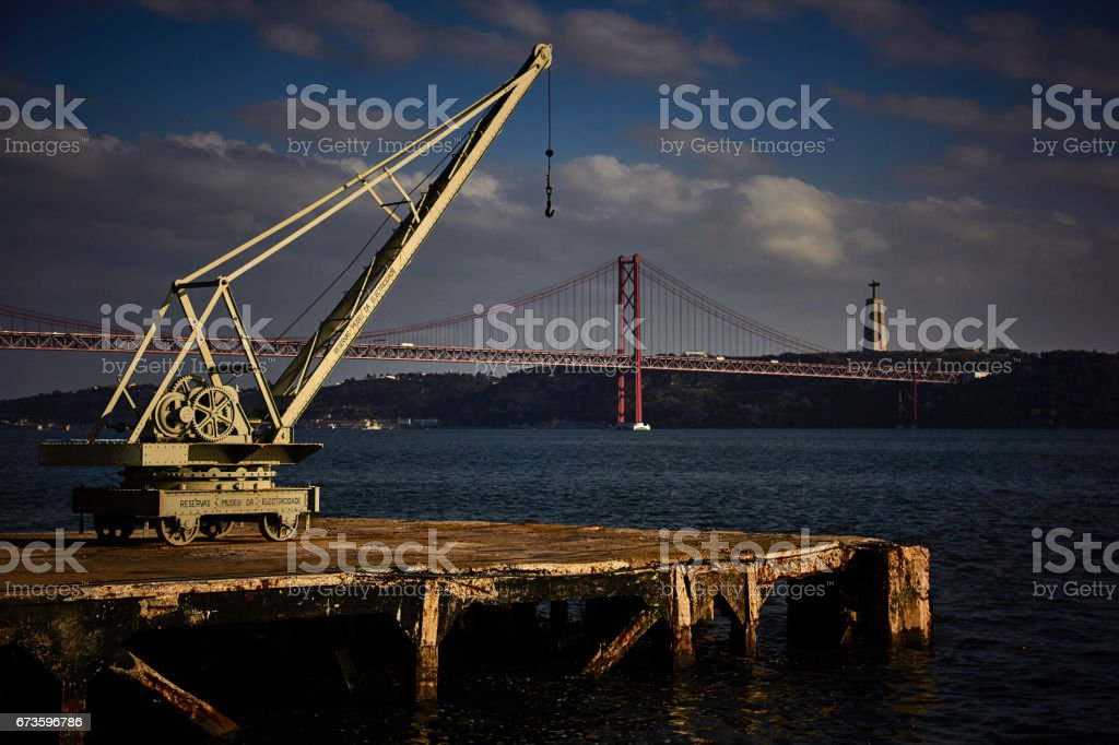 Crane and 25 de Abril Bridge stock photo