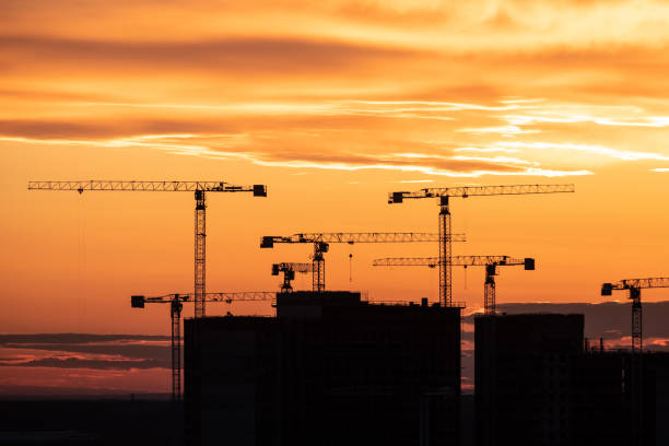 Crane and building silhouettes at sunrise. Abstract Industrial background with construction cranes silhouettes over amazing sunset sky stock photo