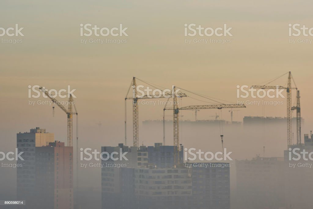 Crane and construction site in urban smog stock photo