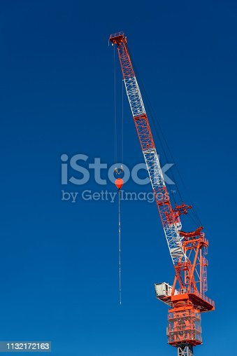 Construction fixed crane with cabin and hook at work against a blue sky