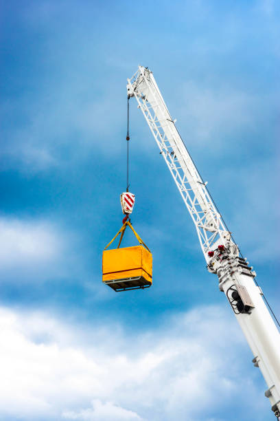 Crane Boom with Container Crane boom with hook lifting a yellow container in harbor against blue sky. rigging stock pictures, royalty-free photos & images