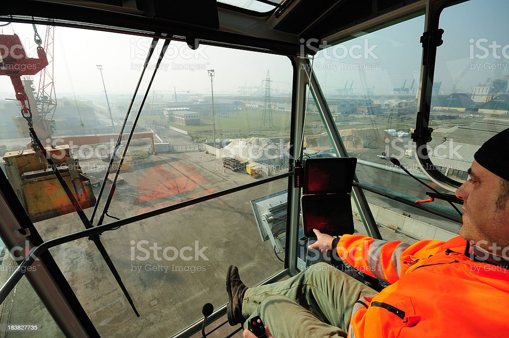 Crane cabin view and operator A man operating a high crane with docks in the background Activity Stock Photo