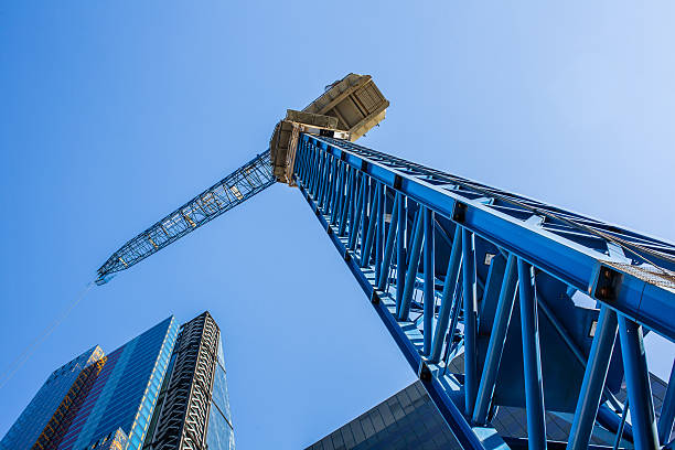 crane construction over modern building - crane construction machinery stock pictures, royalty-free photos & images