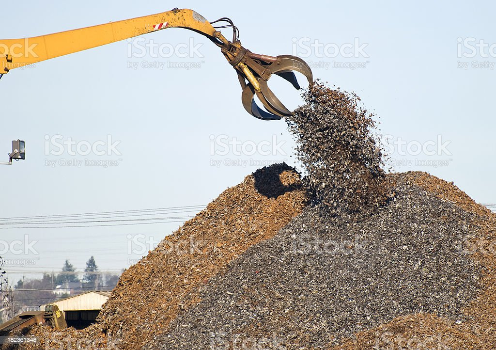 Crane dropping shredded scrap metal on pile royalty-free stock photo