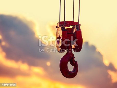 crane hook hanging in the air at sunset