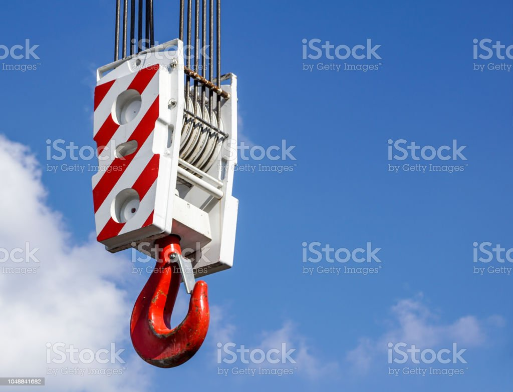 Crane hook with red and white stripes hanging, blue sky in background - foto stock